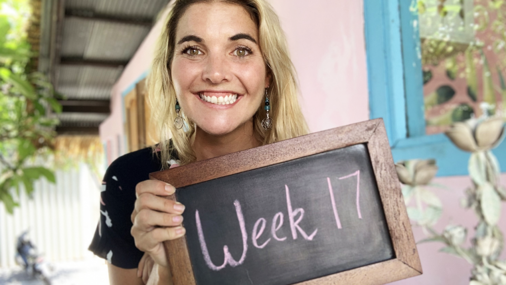 "Abbey holding a chalkboard that says, ""week 17"""
