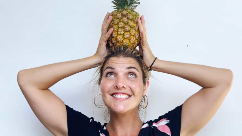 Abbey holding a pineapple on top of her head